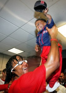 Boston Red Sox pitcher Pedro Martinez lifts his friend Nelson, from the Dominican Republic, during their locker room celebration after the Red Sox beat the Anaheim Angels 8-6 in Game 3 of the American League Division Series, in Boston October 8, 2004. The Red Sox swept the series three games to none. REUTERS/Jessica Rinaldi